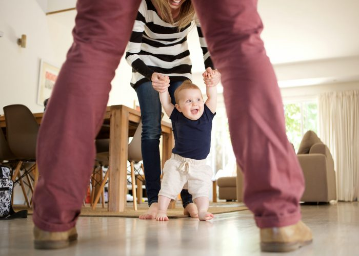 Portrait of cute baby boy learning to walk with mother and father at home
